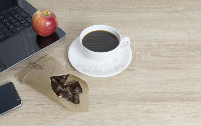 Working place at wooden table, Coffee-break. Top view of working place elements,Working wooden table with empty space, laptop, apple, coffee cup, dark chocolate royalty free stock photography