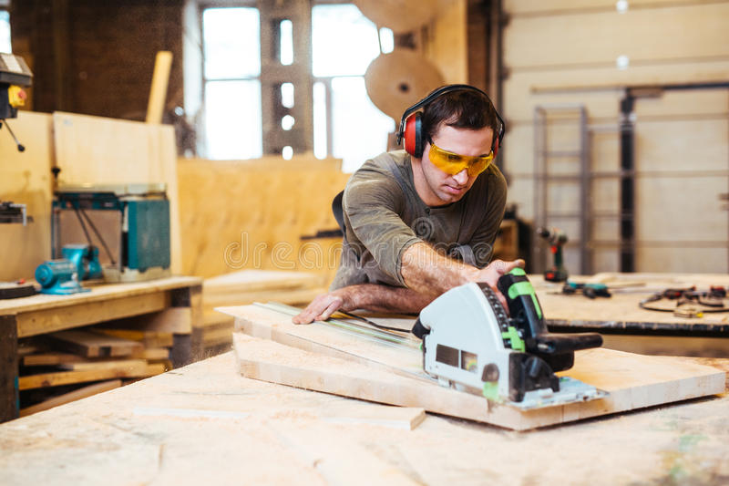 Working with power tool. Young carpenter working with wood-router royalty free stock image
