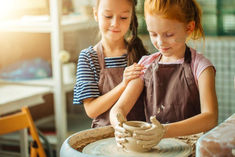 Working process with clay potter wheel. Two girls making pottery in studio royalty free stock photo