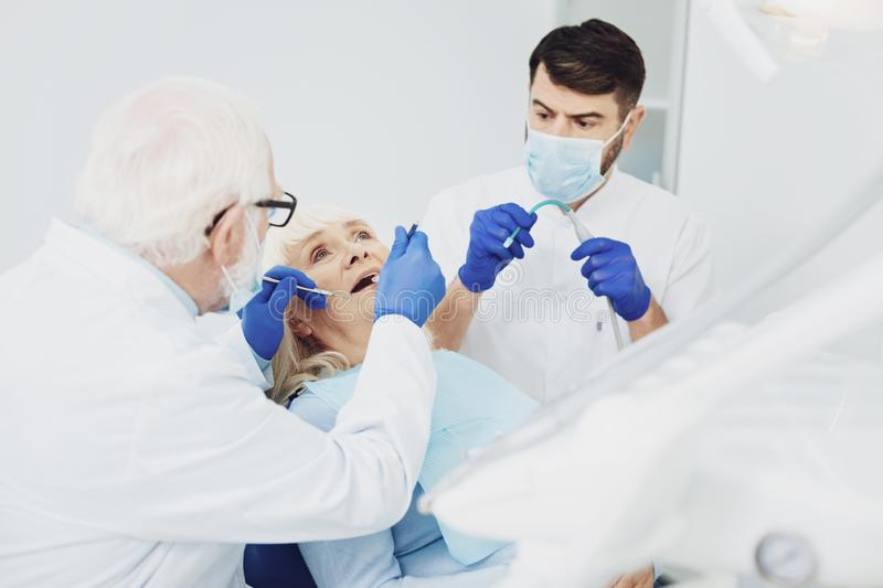 Experienced male dentists treating patient stock image