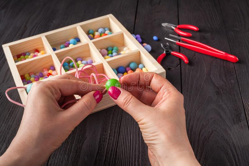 Working process. Handcraft concept. Creative woman making beautiful beads of colorful balls stock image