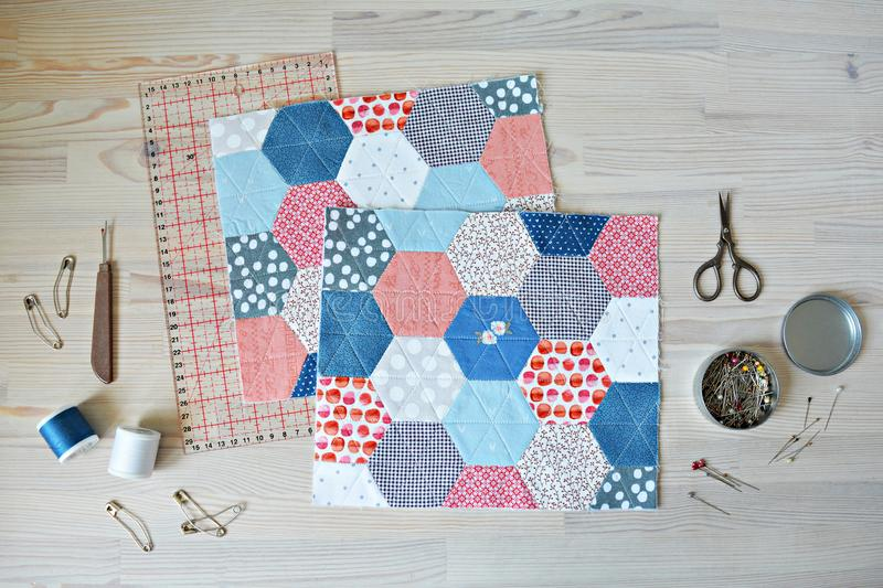 Working process: hexagon quilt, threads, retro scissors, pins, metal jar, quilting ruler and seam ripper. On the wooden table royalty free stock photo