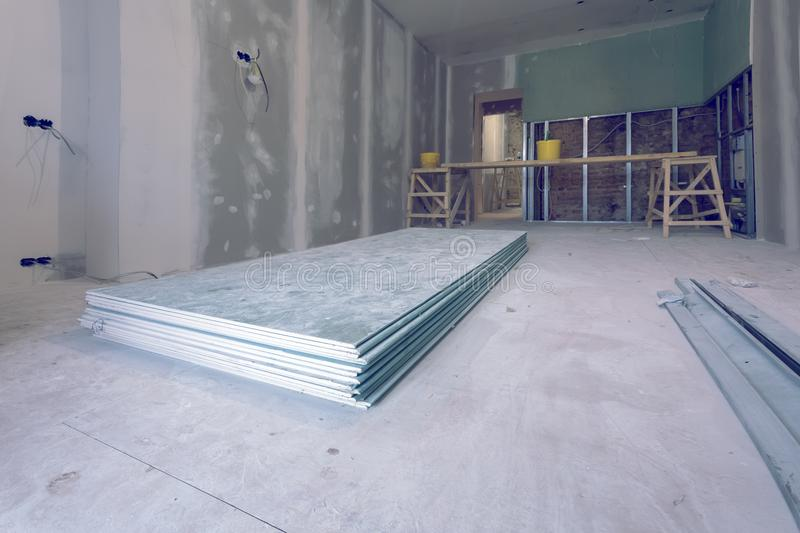 Working process of installing metal frames and plasterboard drywall and materials in apartment is under construction stock image