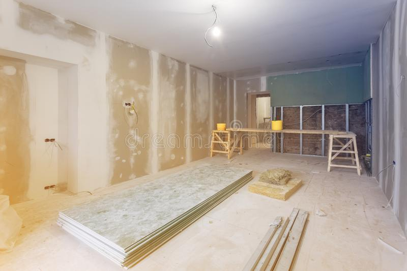 Working process of installing metal frames and plasterboard drywall for gypsum walls and materials are in apartment is under con stock photography