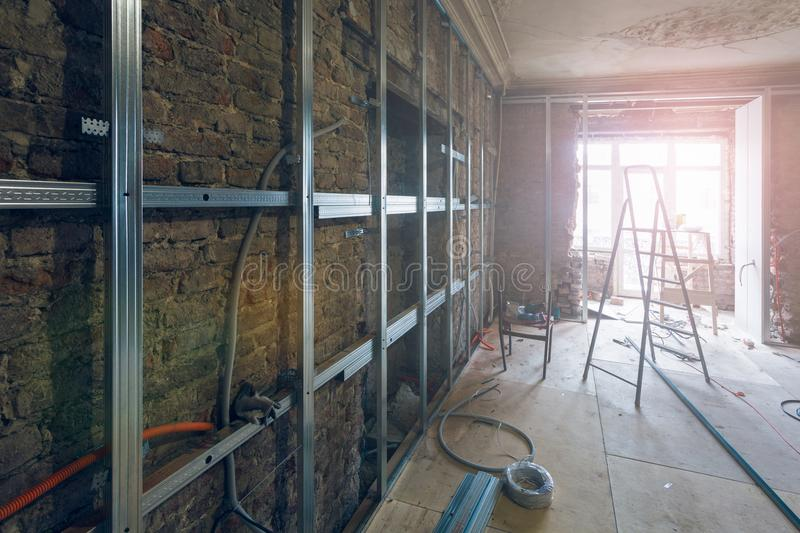 Working process of installing metal frames for plasterboard drywall for making gypsum walls with ladder and tools in apartment i stock images
