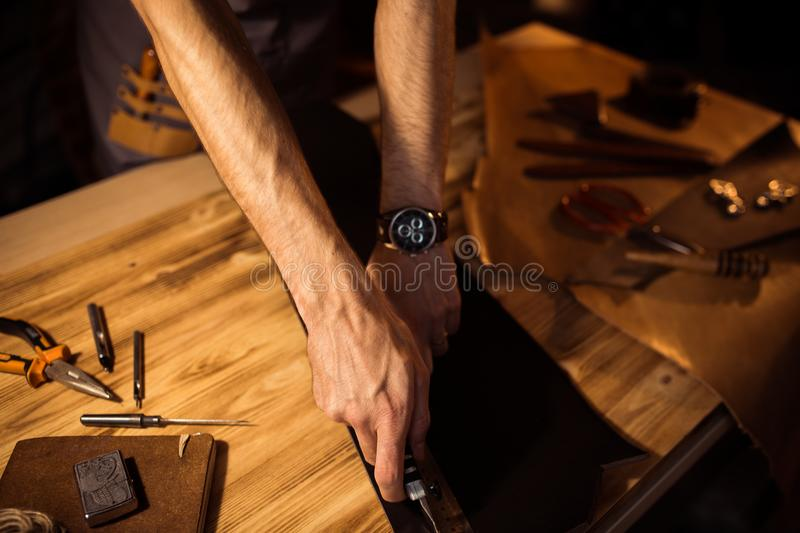 Working process of the leather belt in the leather workshop. Man holding crafting tool and working. Tanner in old. Tannery. Wooden table background royalty free stock photography