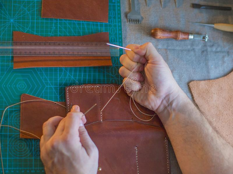 Working process in the leather workshop. Man holding crafting tool and working. He is sewing to make a walet. Tanner in royalty free stock photography