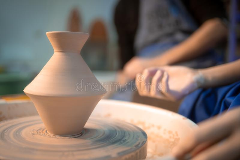 Working process of man`s work at potters wheel in art studio. Unknown craftsman creates jug. Focus on hands only. Small. Business, talent, invention royalty free stock images
