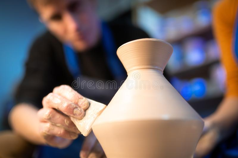 Working process of man`s work at potters wheel in art studio. Unknown craftsman creates jug. Focus on hands only. Small. Business, talent, invention royalty free stock photos