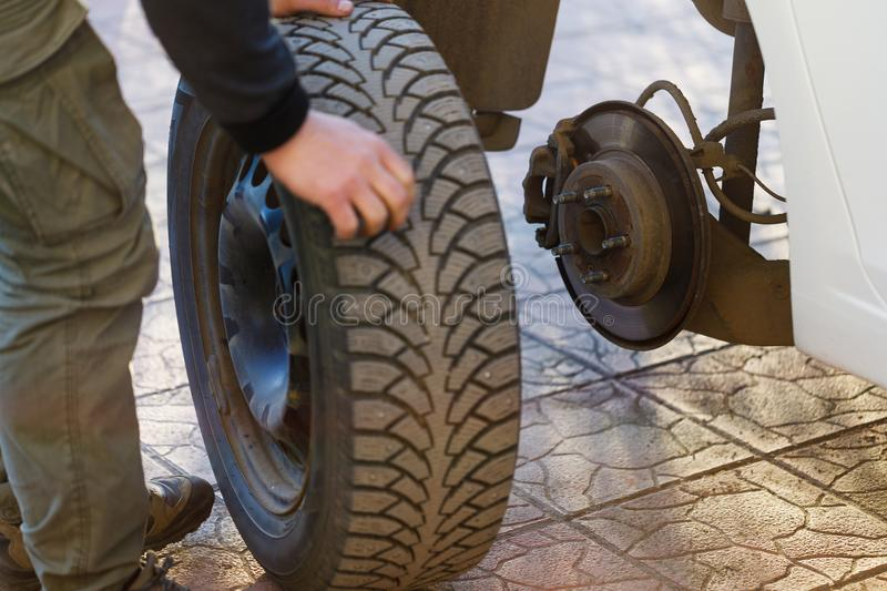 Removal of a car wheel and replacement of winter tires for summer royalty free stock photography