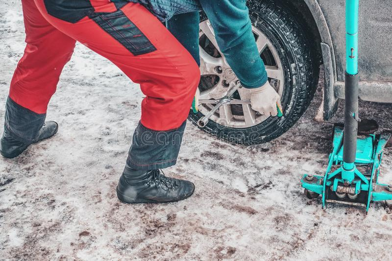 The working process of removing the wheels from the car on the street in the winter. Replacing winter tires for summer royalty free stock photo
