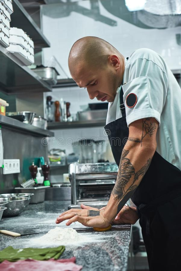 Working process. Vertical photo of handsome professional chef with tattoos on his hands kneading the dough in restaurant stock photo