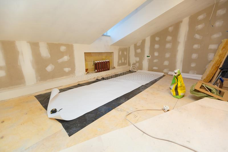 Working process of wallpapering on the drywall in small room apartment is under construction, remodeling, renovation. Extension, restoration and reconstruction stock photo