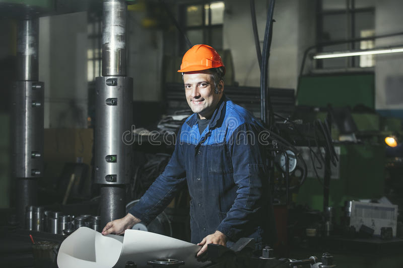 Working in production against a background of machines from the. Engineering drawings in his hands while working stock image