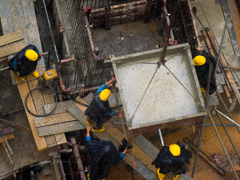 Working in the Rain. Emptying a cement bucket in the rain stock photography