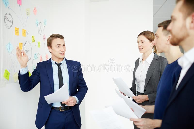Working seminar. Confident manager or employer standing by whiteboard and explaining young specialists some working points stock photos