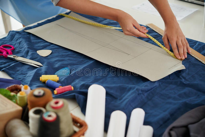 Working with sewing pattern. Hands of tailor measuring sewing pattern on textile royalty free stock images