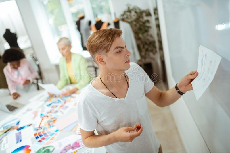 Motivated blond young man looking at his sketch. Working on a sketch. Motivated blond young men looking at his sketch while holding a red magnet in his hand royalty free stock photography