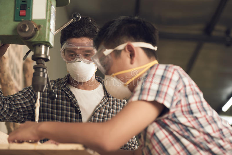 Working with son. Vietnamese men looking how his son working with drill machine royalty free stock photo