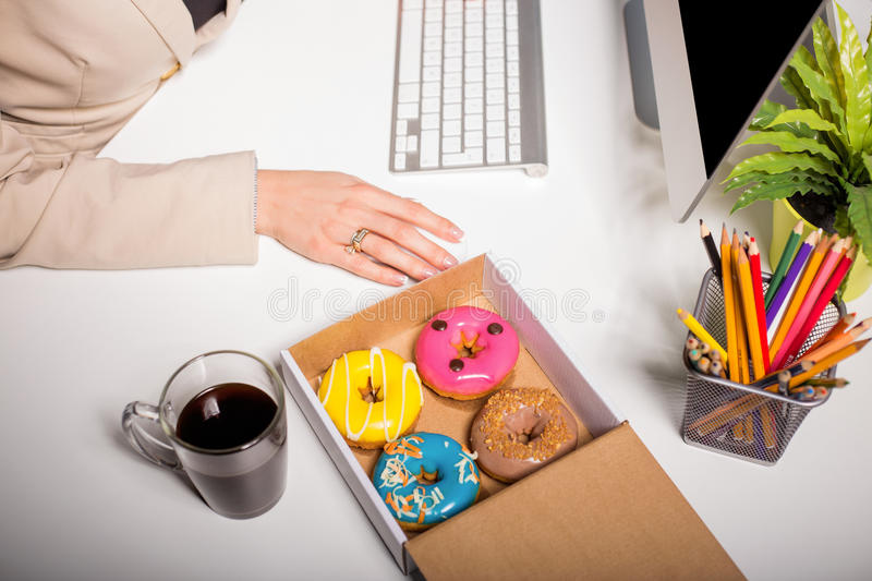 Working space with coffee and donuts royalty free stock photography