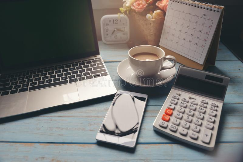 Working space at home.Office desk with Cup of Coffee,Desktop laptop,Calendar 2019,clock and pot of rose flower on blue wooden desk. Working space at home.Office royalty free stock photos