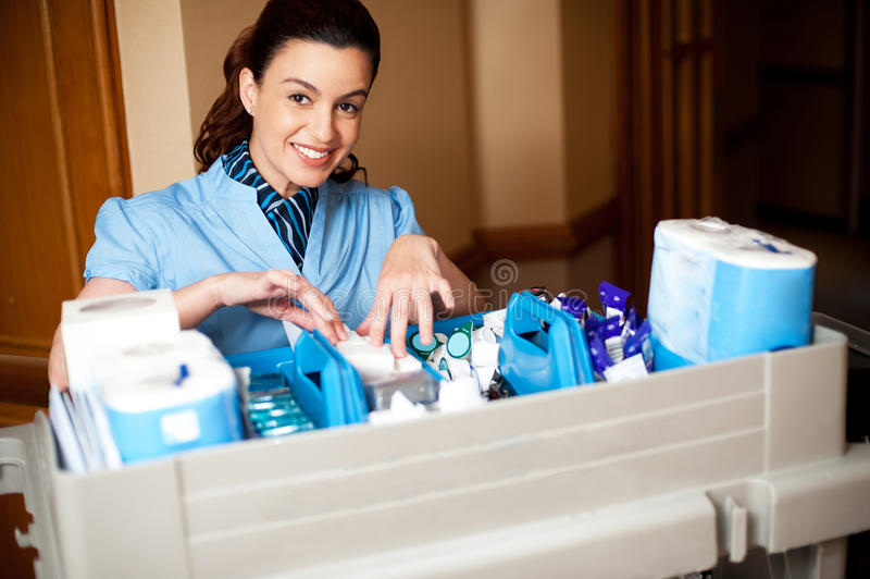 Working staff arranging toiletries in a wheel cart. Looking at camera and smiling royalty free stock photo