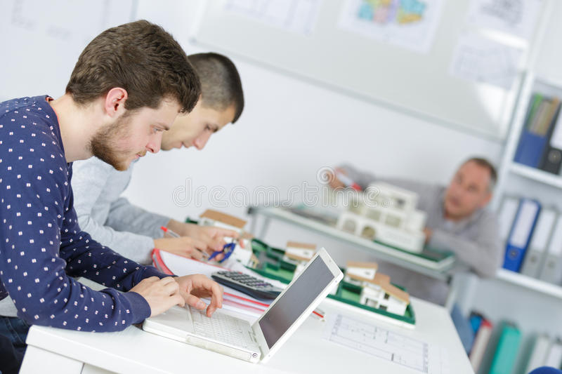 Working students in classroom with laptops. Working students in a classroom with laptops royalty free stock image