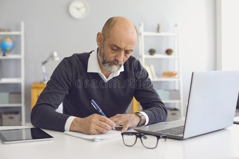 Working and studying from home. Thoughtful mature man taking notes during online business meeting or webinar royalty free stock photos