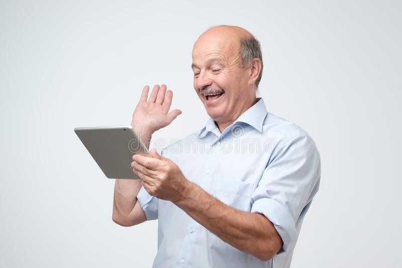 Cheerful mature european man chatting with his friends online using tablet computer royalty free stock images