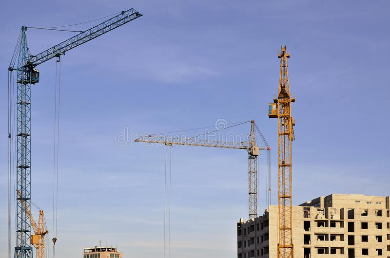 Working tall cranes inside place for with tall buildings under construction against a clear blue sky. Crane and building working royalty free stock photo