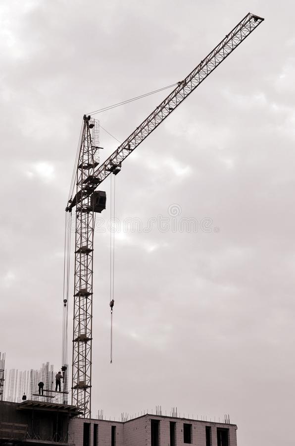 Working tall cranes inside place for with tall buildings under construction against a clear blue sky. Crane and building working royalty free stock photography