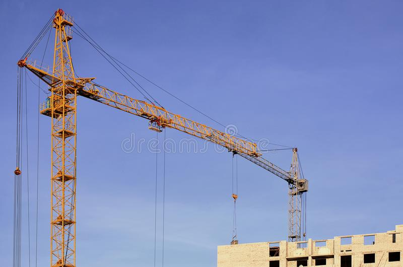 Working tall cranes inside place for with tall buildings under construction against a clear blue sky. Crane and building working stock images