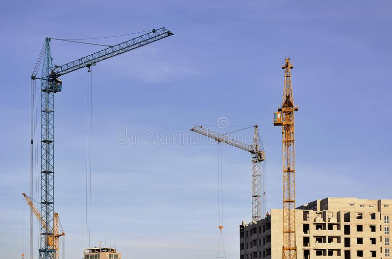 Working tall cranes inside place for with tall buildings under construction against a clear blue sky. Crane and building working royalty free stock photos