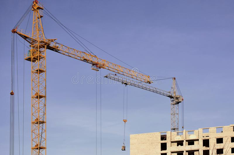 Working tall cranes inside place for with tall buildings under construction against a clear blue sky. Crane and building working royalty free stock images