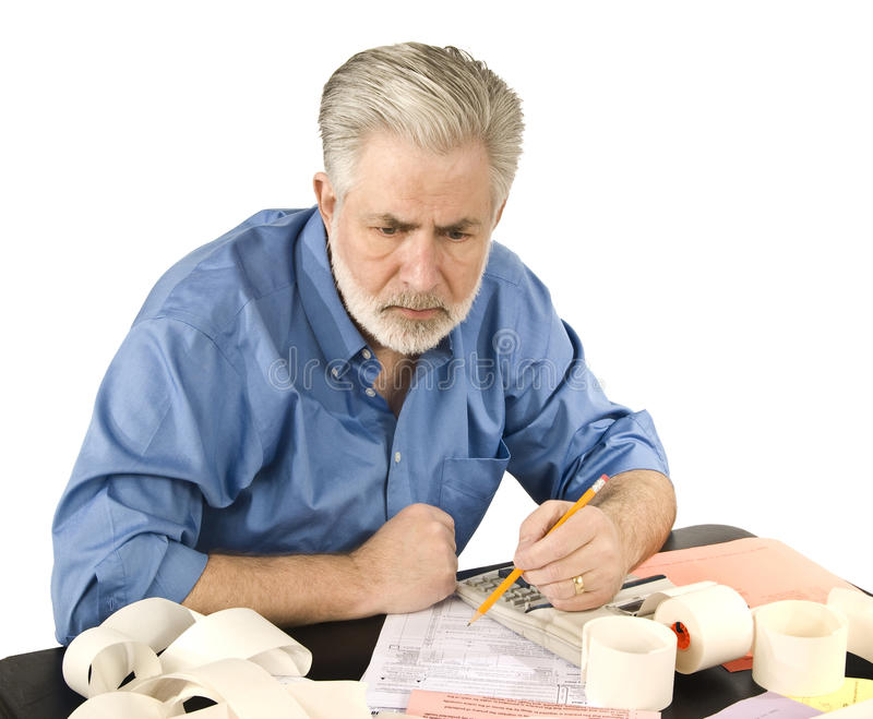 Working On Taxes. A mature man working his taxes royalty free stock photo