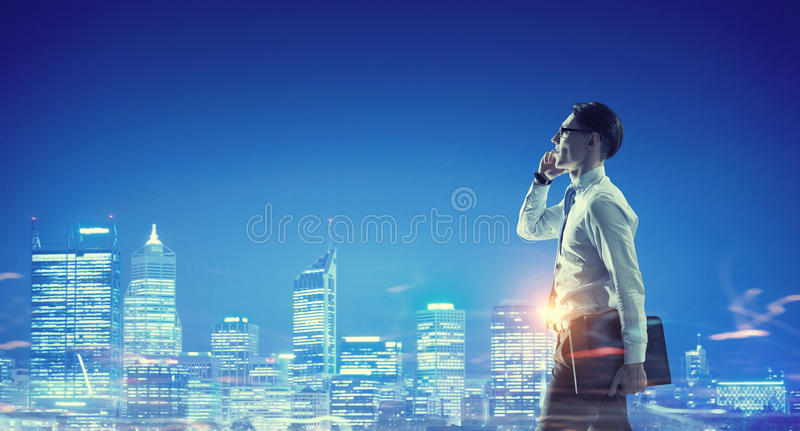 Working till late night . Mixed media. Elegant businessman looking at night glowing modern city stock image