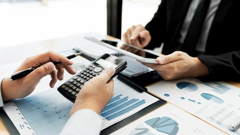 Working together in office concept, young businessmen using touchpad digital tablet to discuss the situation on the market or stoc. K yield graph chart at stock image