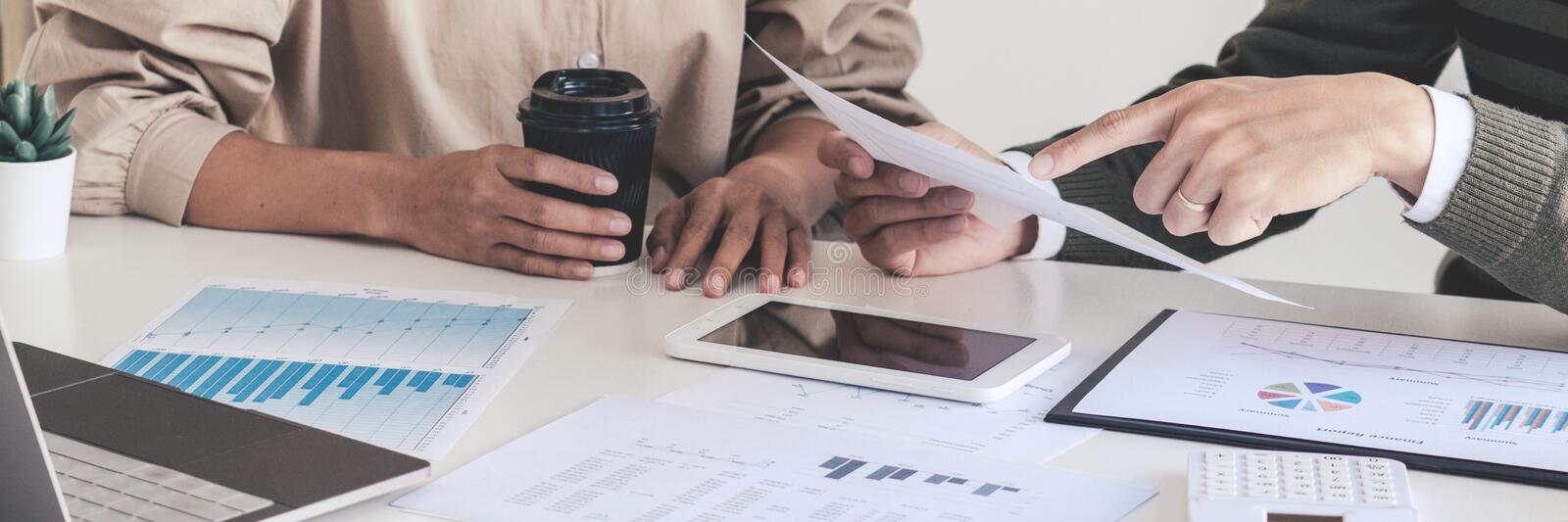 Working together on project, Two young business colleagues working or meeting with partner discussing financial documents and idea royalty free stock photos