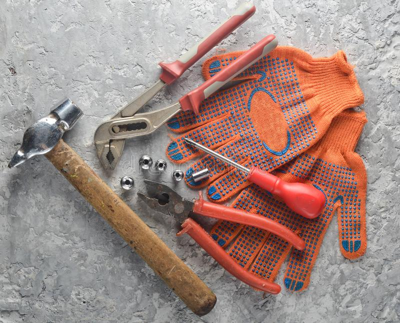 Working tool on a gray concrete surface. Work gloves, hammer, nippers, screwdriver, pliers, screwdriver. Top view stock photos