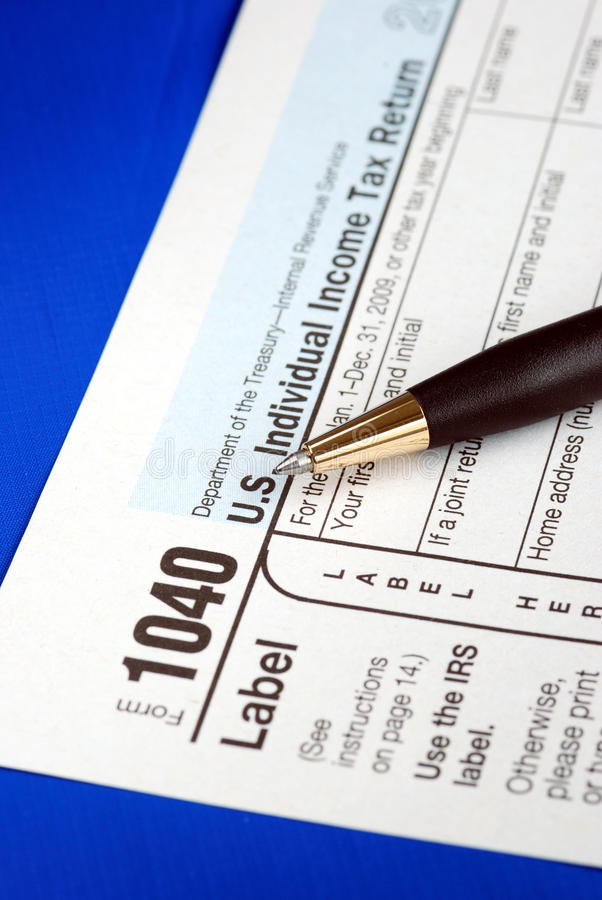Working on the United States Income Tax 1040. Isolated on blue royalty free stock photography