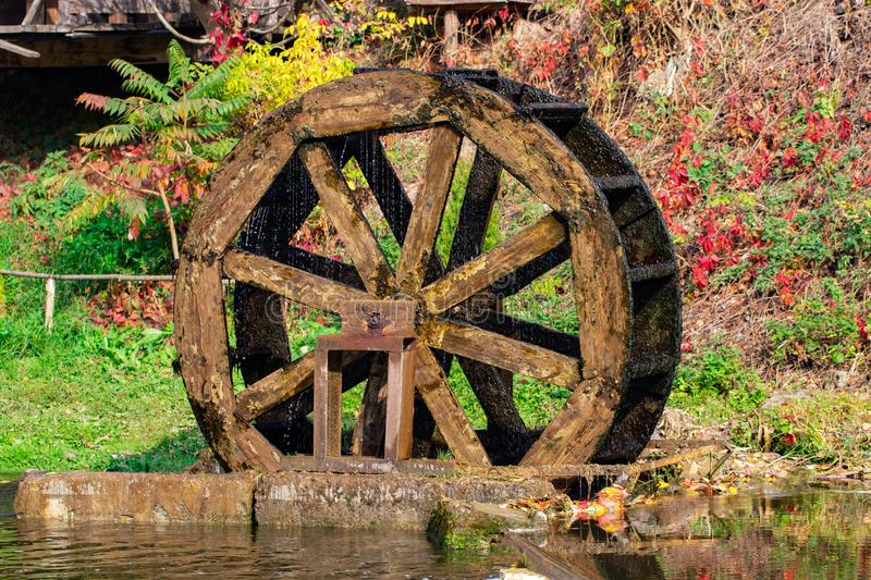 Working watermill wheel with falling water in the village.  stock photos
