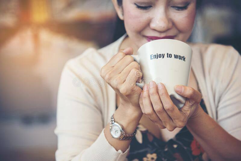 Working woman drinking coffee cup with text enjoy to work happy face in office. Asian Beautiful Woman Smiling and Relax holding a royalty free stock images