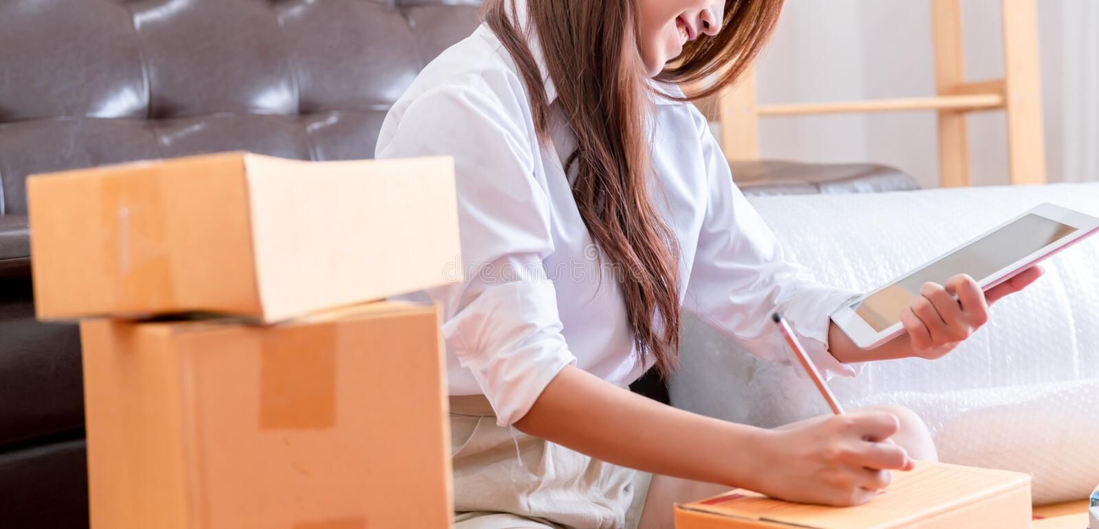 Working woman sme business at office in home interior her checking order from tablet. For customer and online delivery for ready packing in bedroom royalty free stock images