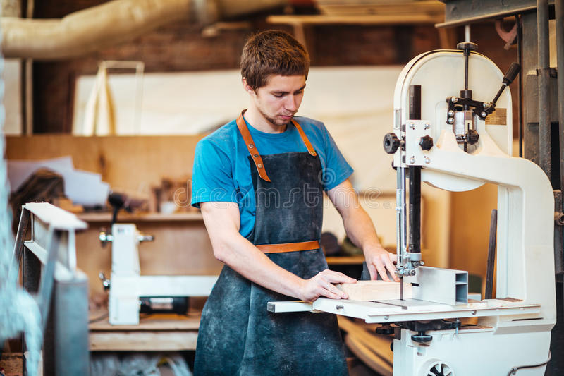 Working with wooden planks. Professional cabinetmaker cutting wooden plank in scroll-saw stock images