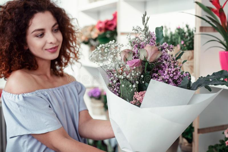Smiling cheerful lady checking her freshly-made bouquet stock image