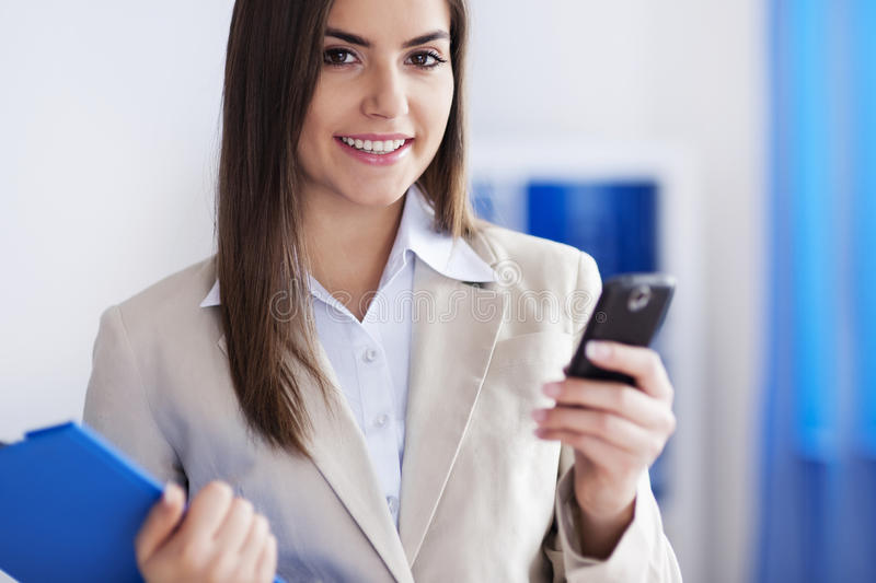 Working young woman. With mobile phone stock image