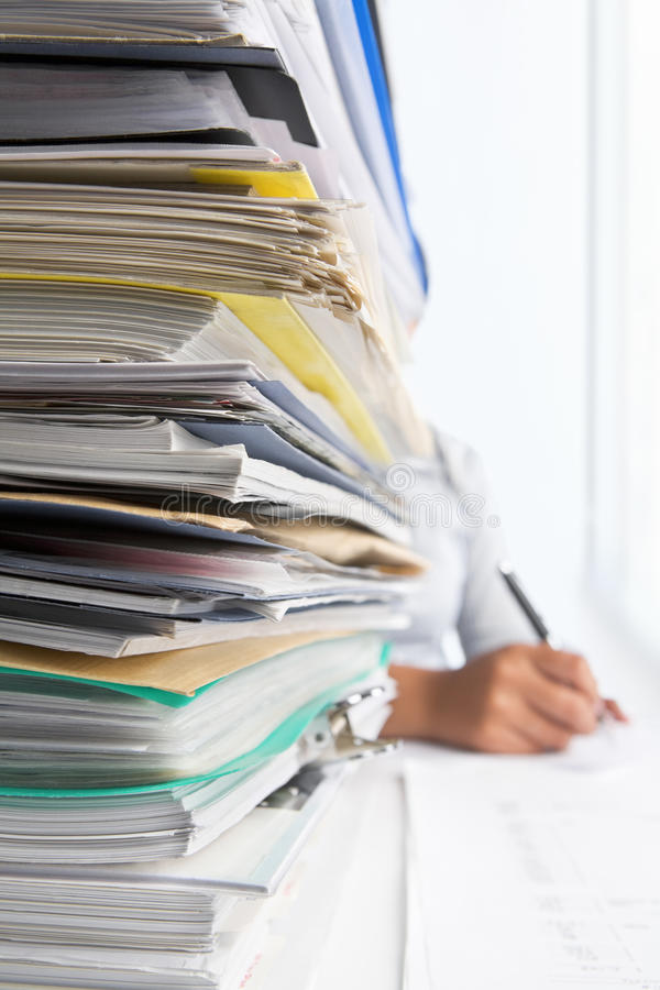 Workload. Concept with high pile of paperwork. Selective focus royalty free stock images
