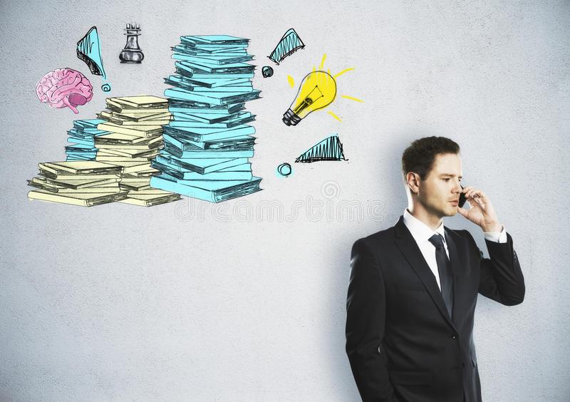 Workload concept. Handsome young businessman talking on the phone on concrete background with drawn paperwork stacks. Workload concept royalty free stock images
