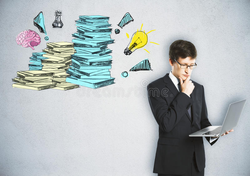 Workload concept. Handsome young businessman using laptop on concrete background with drawn paperwork stacks. Workload concept royalty free stock photo