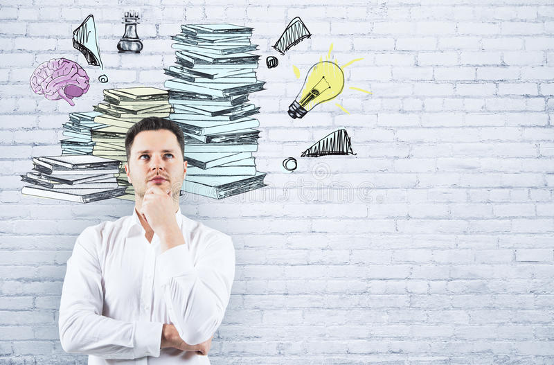 Workload concept. Thoughtful businessman on white brick background with drawn paperwork pile. Workload concept royalty free stock photo